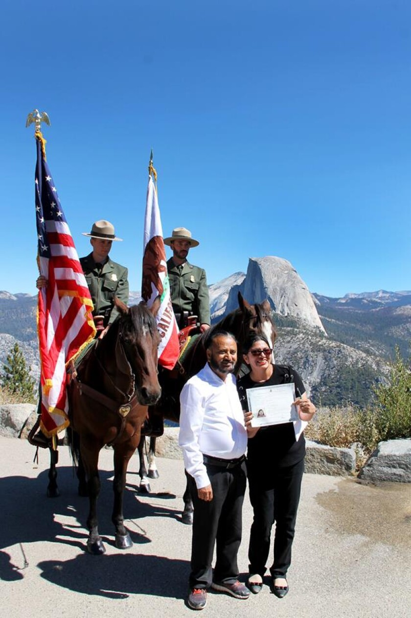 A new citizen shows off her certificate in front of Yosemite National Park's mounted guards.