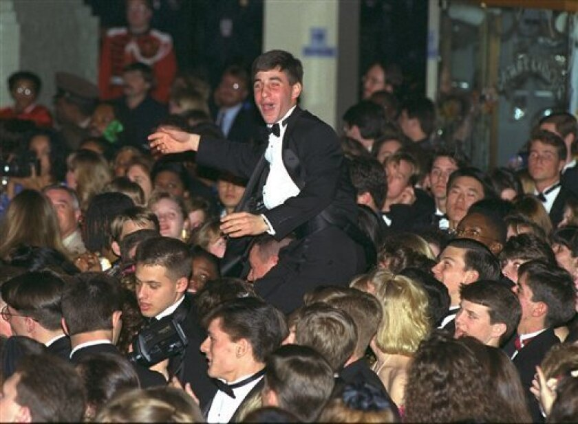 This Jan. 20, 1993 file photo shows a reveler at the Post Office Pavilion as he is carried above the crowd during one of the presidential inaugural balls for President Clinton in Washington.    (AP Photo/Bill Waugh, FILE)