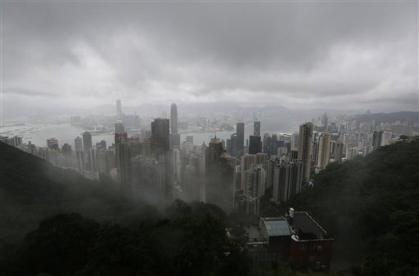 The clouds are hanging low over the city of Hong Kong, seen from the Victoria Peak, in Hong Kong Tuesday, Aug. 13, 2013. The Observatory said Typhoon Utor intensified slightly as it moves towards the western coast of Guangdong. The typhoon battered the northern Philippines on Monday, toppling power lines and dumping heavy rain across cities and food-growing plains. (AP Photo/Kin Cheung)