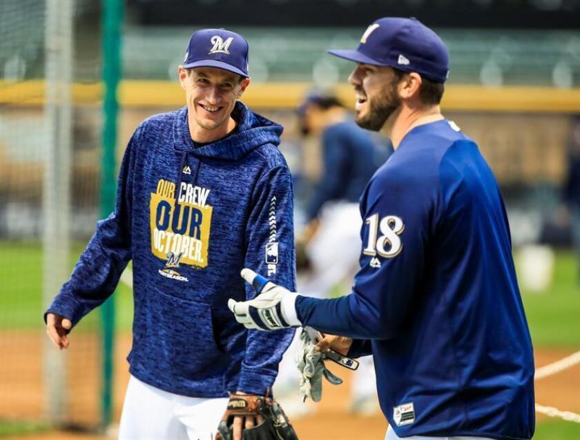 El mánager de los Cerveceros Craig Counsell (i) bromea con el tercera base Mike Moustakas (d) entrena para el partido de la Serie de Campeonato de la Liga Nacional con los Dodgers de Los Angeles en Miller Park en Milwaukee, Wisconsin, EE. UU.. EFE