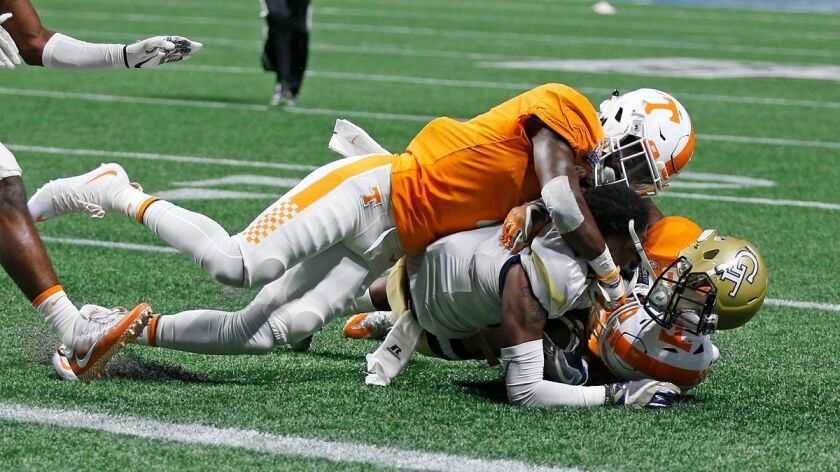 Georgia Tech running back Qua Searcy (1) loses his helmet as he is stopped short of the goal line by Tennessee defensive back Rashaan Gaulden (7) in the second half on Mondau.