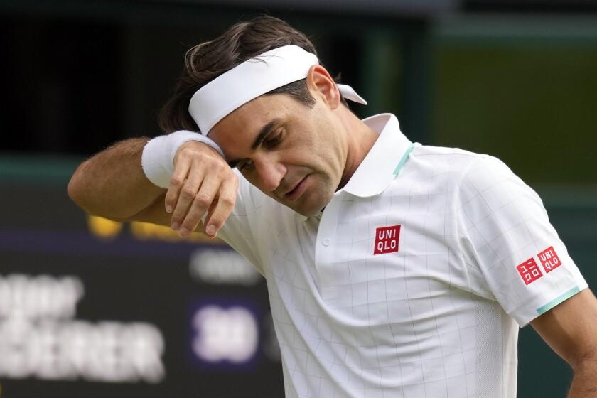 ARCHIVO - En imagen de archivo del 7 de julio de 2021, el suizo Roger Federer se limpia el sudor durante un partido.