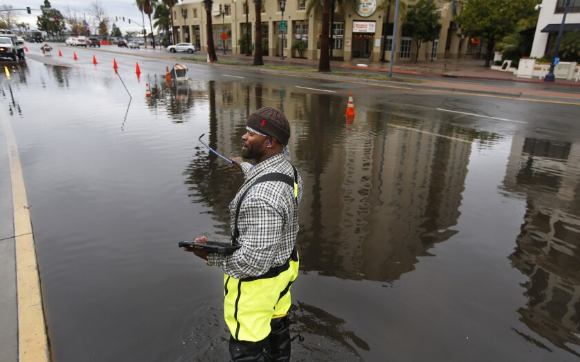 Douglas Owens, with the City of San Diego, monitors an area that flooded along Harbor Blvd. in downtown San Diego on Dec. 23, 2019. The area backs up with water when it rains and there is a high tide.