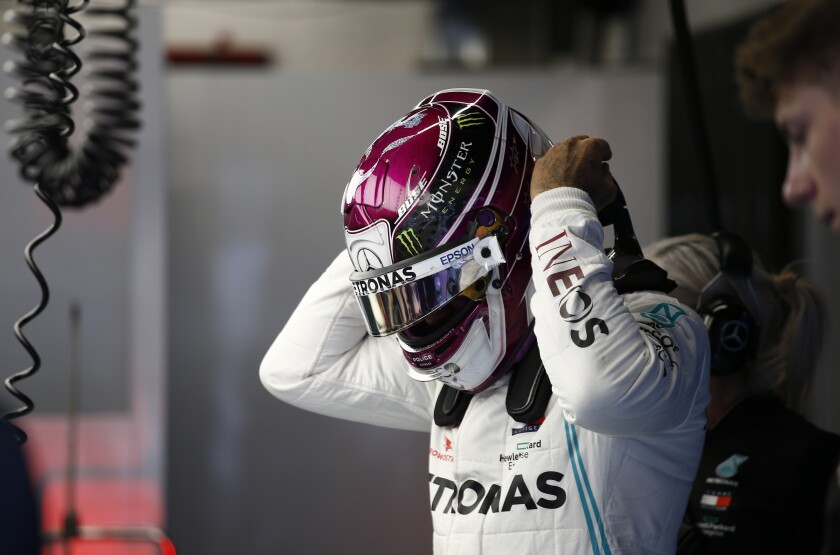 Mercedes driver Lewis Hamilton of Britain adjusts his helmet in the pit lane during the Formula One pre-season testing session at the Barcelona Catalunya racetrack in Montmelo, outside Barcelona, Spain, Friday, Feb. 28, 2020. (AP Photo/Joan Monfort)