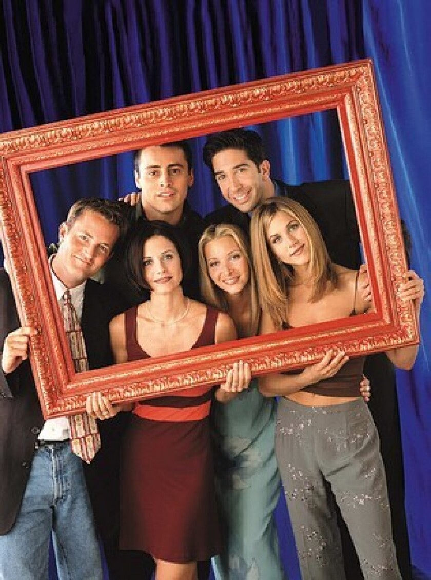 "The cast of ""Friends"" holding a large photo frame around themselves."
