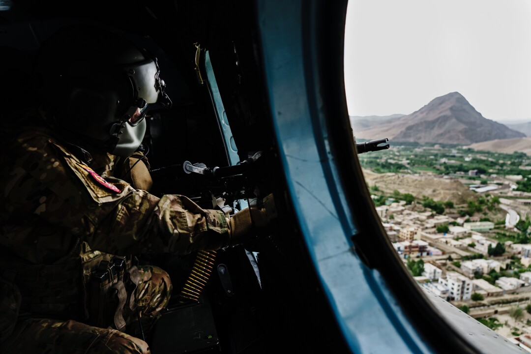 A soldier looks out of a helicopter.