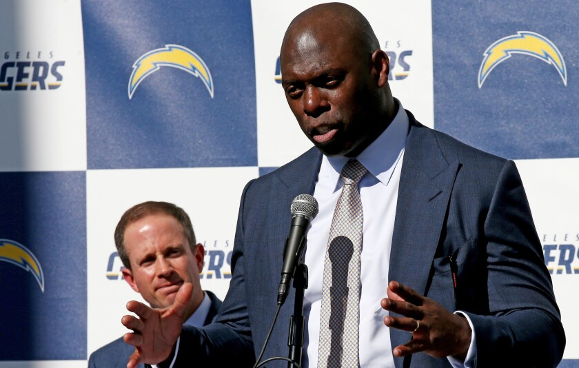 New Chargers Coach Anthony Lynn, right, talks with reporters during a news conference to announce his hiring on Jan. 17 at StubHub Center in Carson.