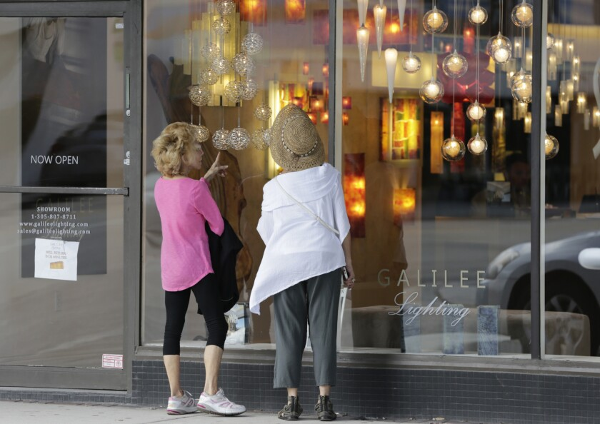Shoppers stop to look in the window of a lighting store in the Design District of Miami Beach, Fla., on Feb. 3.