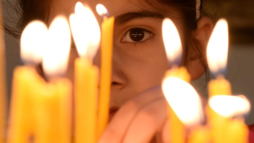 A girl places a candle at the cathedral in Etchmiadzin, Armenia, outside Yerevan, ahead of a ceremony marking the Armenian genocide.