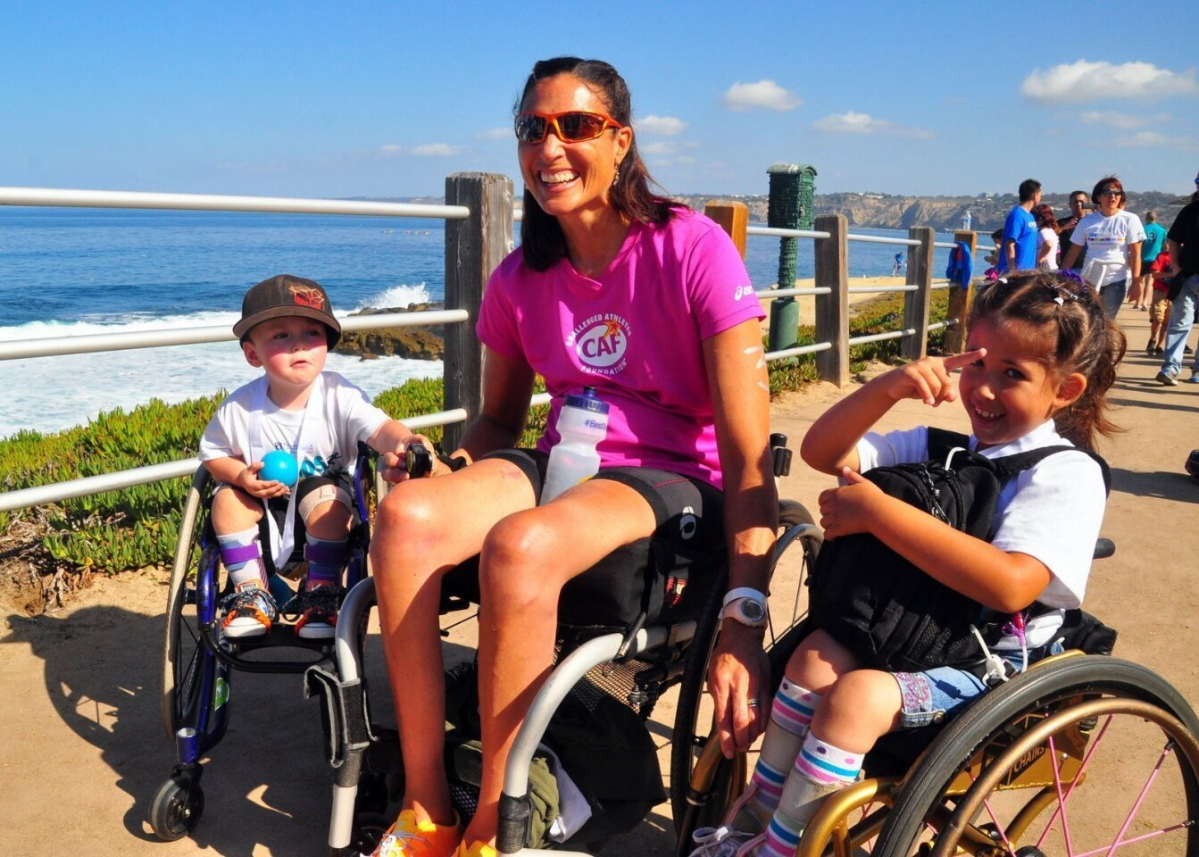 Tricia Downing of Denver, Colorado makes new friends with 3-year-old Abel Rose and 6-year-old Emma Mondragon. The smiles say it all! — at the Challenged Athletes Foundation's 21st annual San Diego Triathlon Challenge Oct. 19, 2014 at La Jolla Cove.