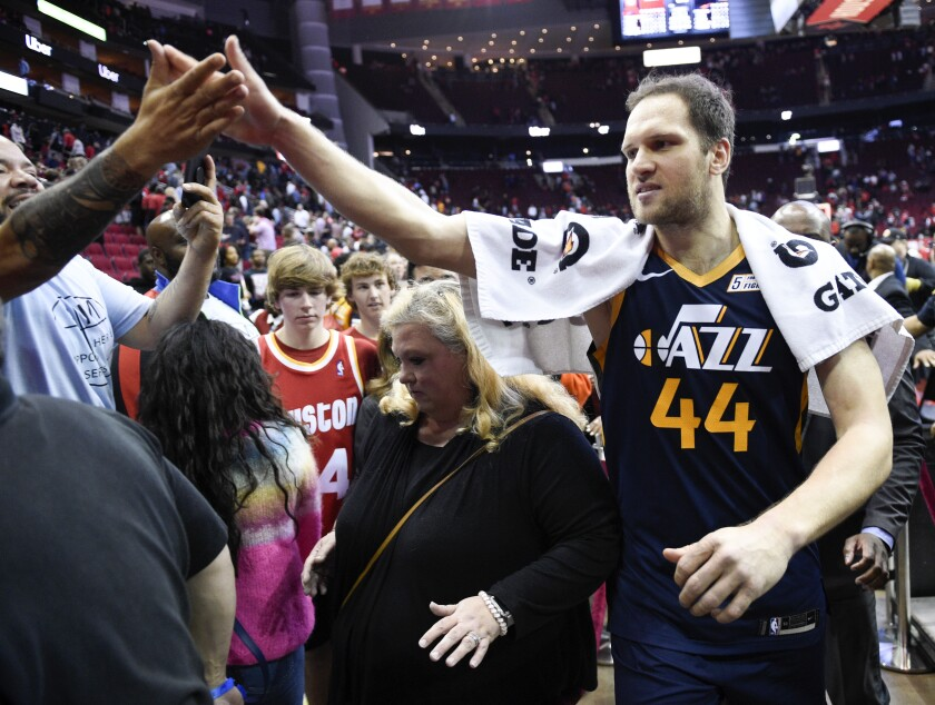 Utah Jazz forward Bojan Bogdanovic (44) high-fives a fan after shooting the game-winning three point basket during the second half of an NBA basketball game against the Houston Rockets, Sunday, Feb. 9, 2020, in Houston. (AP Photo/Eric Christian Smith)