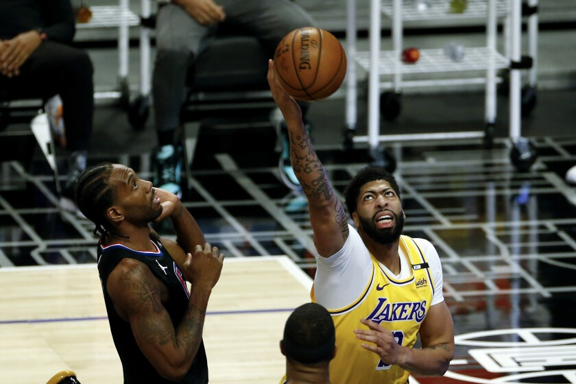 Lakers forward Anthony Davis grabs a rebound next to Clippers forward Kawhi Leonard.