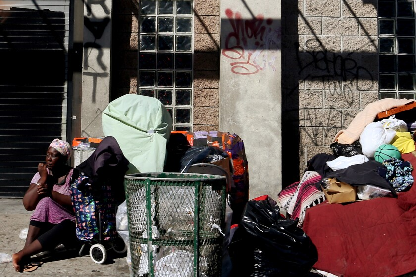 A woman sits beside her belongings on the sidewalk along 6th Street in Los Angeles.