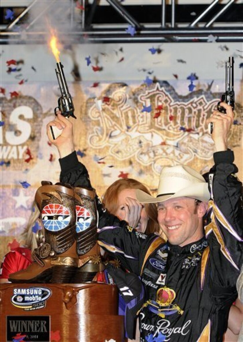 Matt Kenseth fires blanks from revolvers as he celebrates following his win in the NASCAR Sprint Cup Series auto race at Texas Motor Speedway on Saturday, April 9, 2011, in Fort Worth, Texas. (AP Photo/Larry Papke)