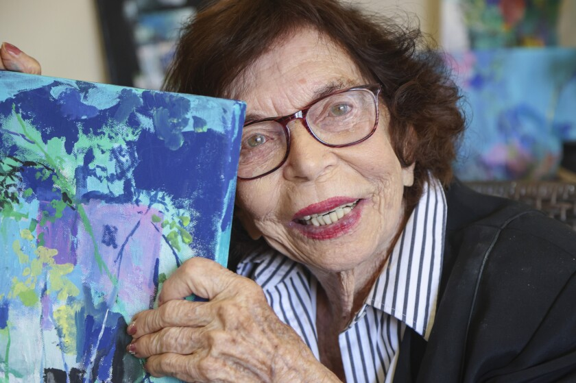 Artist Sue Whitman, 104, poses for a photo with one of her recent paintings on July 20 at her home in San Marcos, CA.