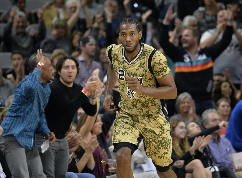 San Antonio Spurs forward Kawhi Leonard runs up court after scoring a basket during the first half of an NBA basketball game against the Charlotte Hornets, Saturday, Nov. 7, 2015, in San Antonio. (AP Photo/Darren Abate)