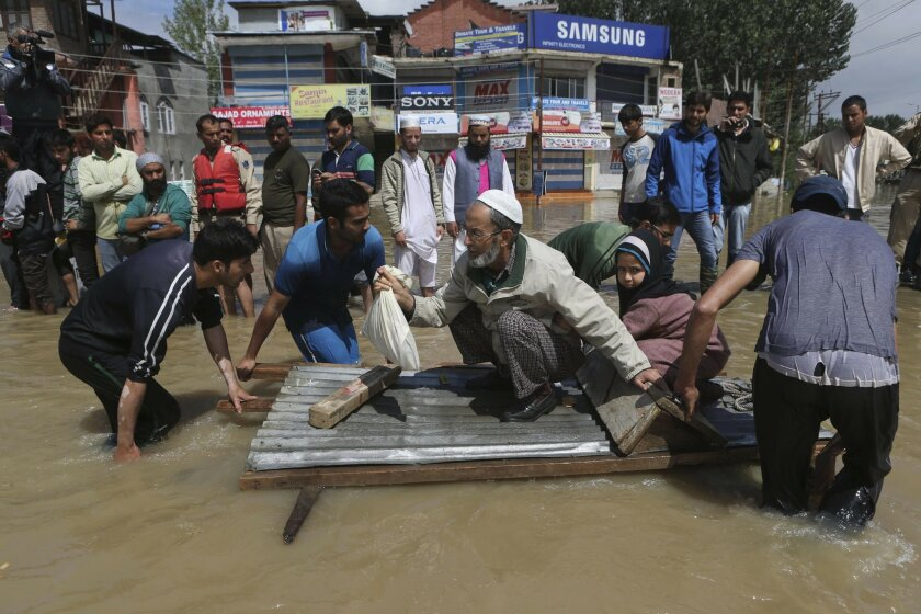 Kashmiri men use a makeshift raft to evacuate an elderly man and his grand daughter from a flooded neighborhood in Srinagar, India, Sunday, Sept.7, 2014. Fast-moving floodwaters submerged large parts of the main city in Indian-controlled Kashmir on Sunday after five days of pounding rain. The flooding, the worst in 50 years, has killed at least 120 people across the Himalayan region.(AP Photo/Dar Yasin)