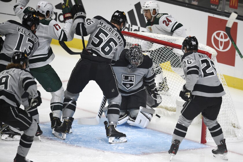Kings goaltender Jonathan Quick, center, looks down after allowing a goal to Minnesota Wild defenseman Mathew Dumba.