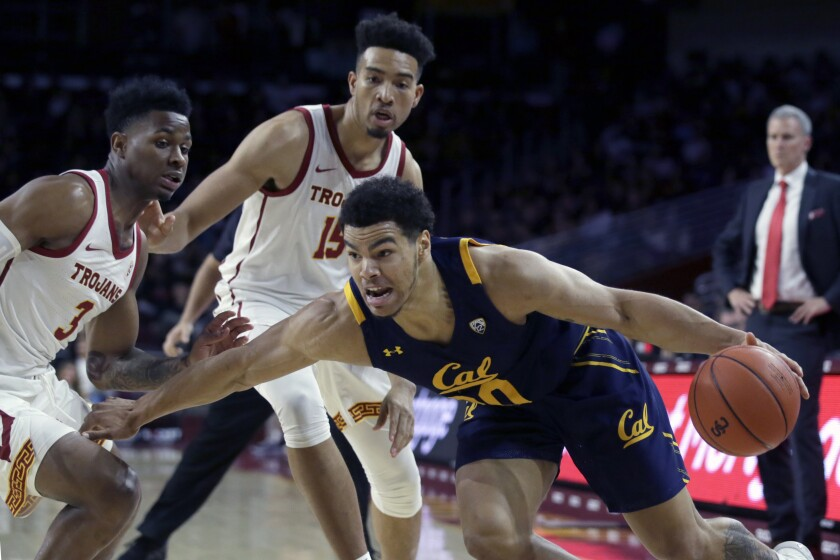 California guard Matt Bradley, right below, drives past USC guard Elijah Weaver, left, and forward Isaiah Mobley during the first half on Thursday at the Galen Center.