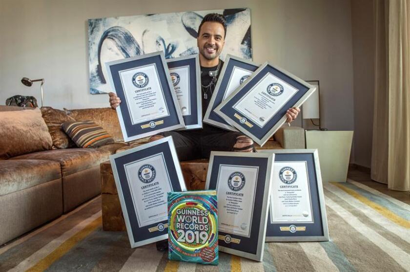 """El cantautor puertorriqueño Luis Fonsi posa con sus siete récords Guinness recibidos por su canción """"Despacito"""" durante un acto de reconocimiento en Miami, Florida. EFE"""