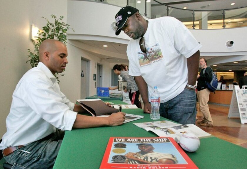 """San Diego artist Kadir Nelson (left) signs a copy of his book """"We Are The Ship: The Story of Negro League Baseball"""" for Adrean Askerneese of Temecula at Grossmont College."""
