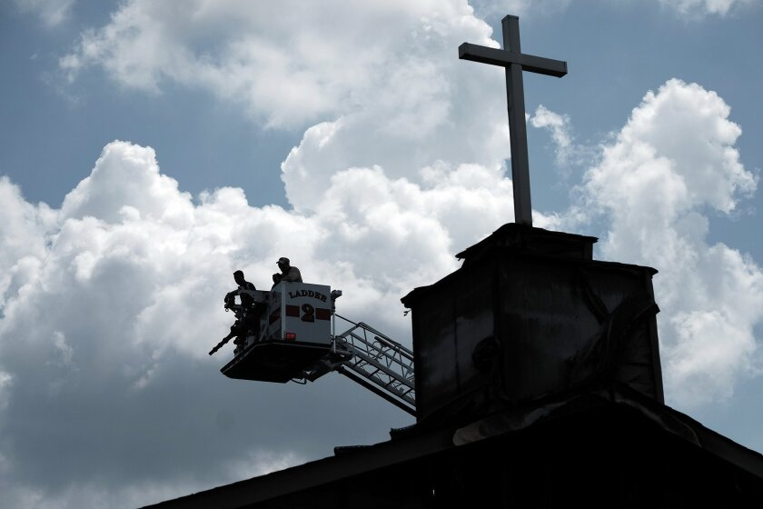 Investigators use a ladder truck to get a bird's-eye view as they try to determine the cause of a fire that destroyed the Glover Grove Baptist Church in Warrenville, S.C.
