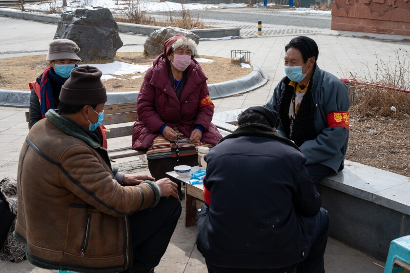 A group of community virus prevention workers sits in protective masks and red armbands in Garzê on Feb. 12, 2020.