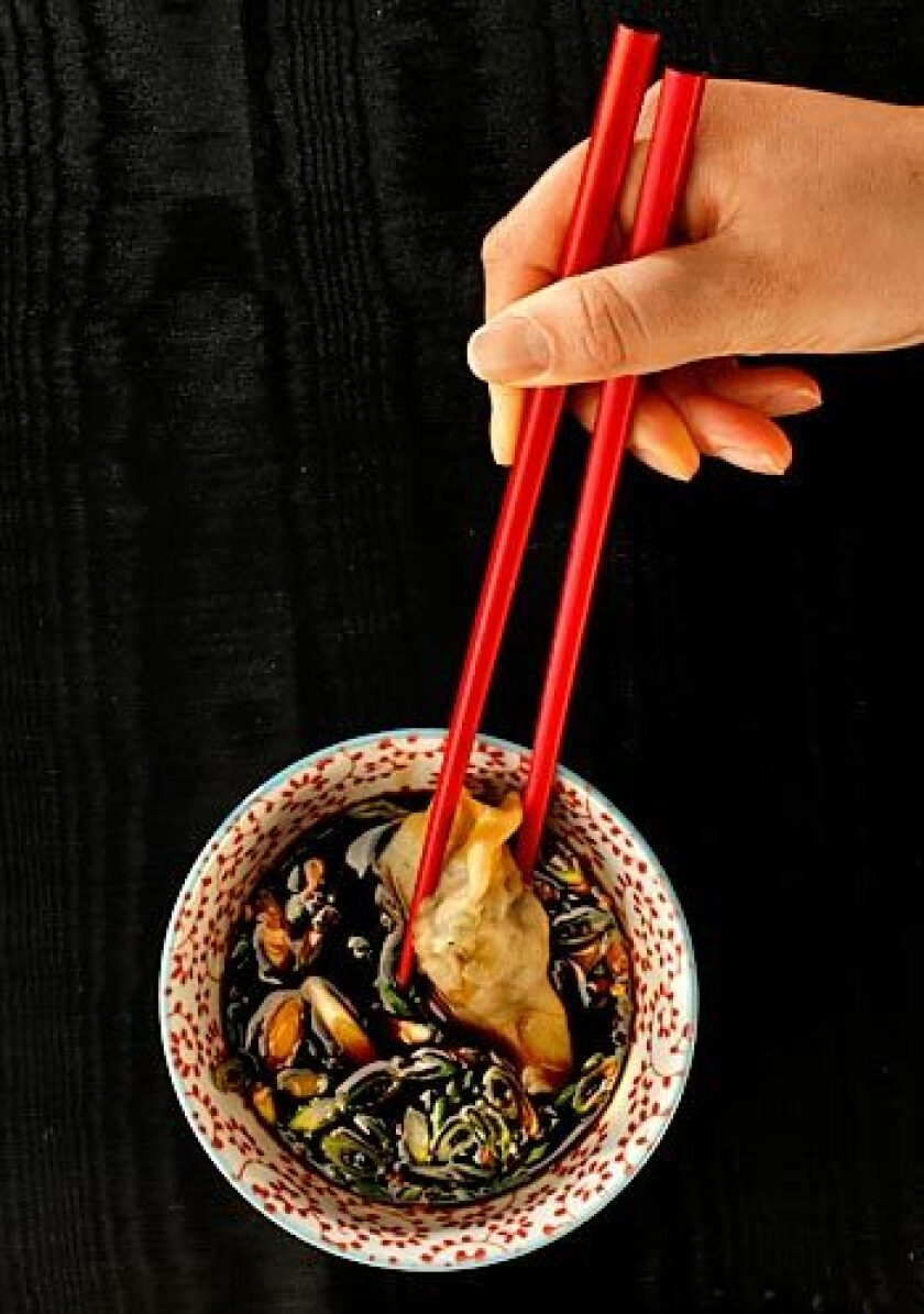 A handmade shrimp dumpling is dipped in black vinegar seasoned with soy sauce.