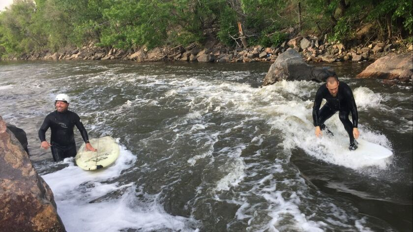 Eric Thomas, left, and Dan Setzke surfing the Beaver Wave in the South Platte River running through