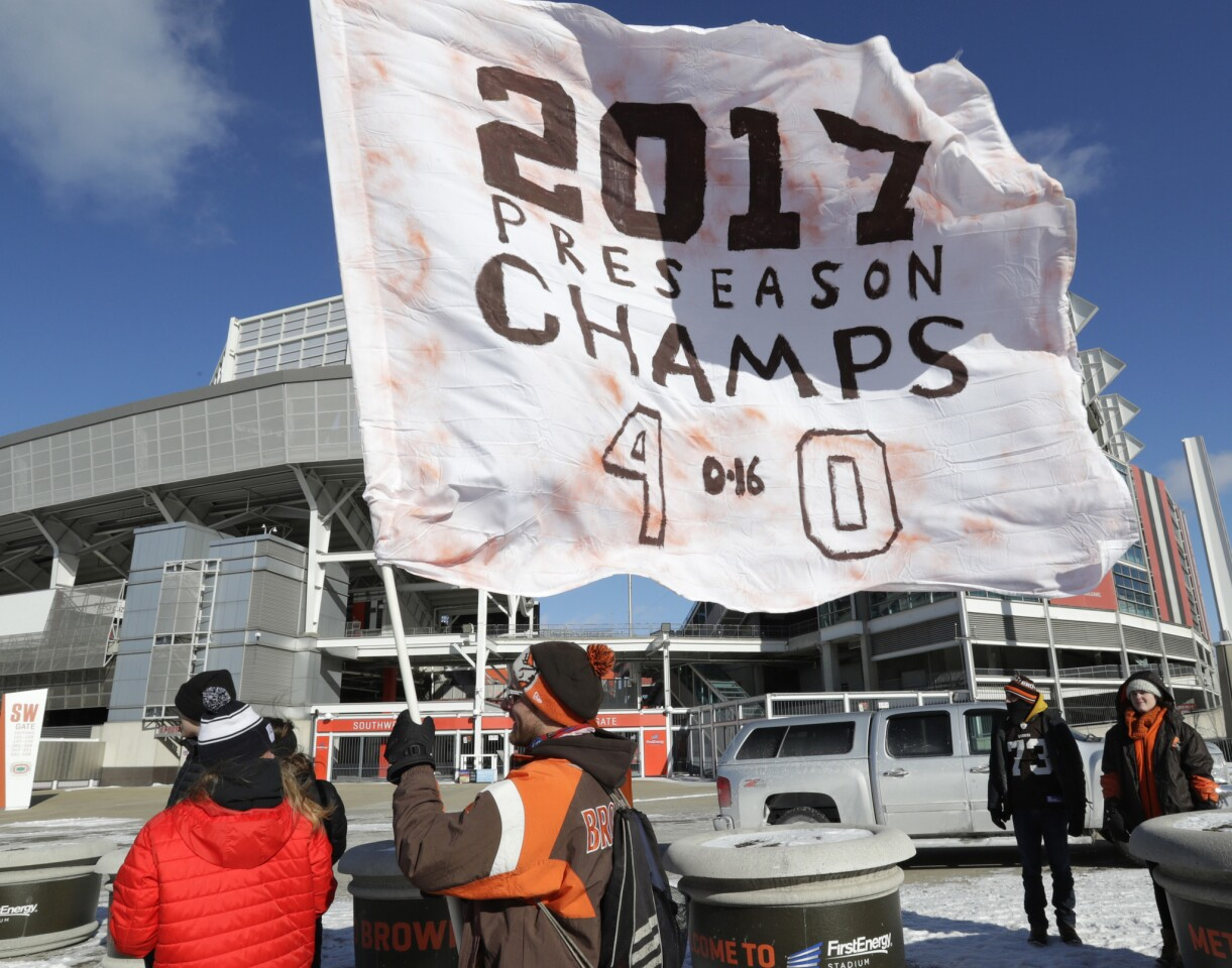 """Matt Hughes holds up a flag during the """"Perfect Season"""" parade on Saturday in Cleveland. The Browns became the second team in NFL history to lose 16 games in a season."""