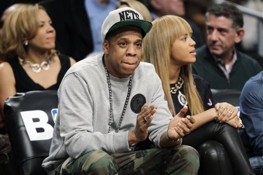 FILE - In this Nov. 26, 2012, file photo, rap mogul and Brooklyn Nets minority owner Jay-Z and his wife, Beyonce, watch an NBA basketball game between the Nets and the New York Knicks at Barclays Center in New York. Jay -Z is selling his stake in the Nets so he can become certified as a player agent, possibly before the end of the season. The process is underway, with paperwork already filed, a person with knowledge of the details said Wednesday, April 10, 2013. NBA rules prevent anyone from bei
