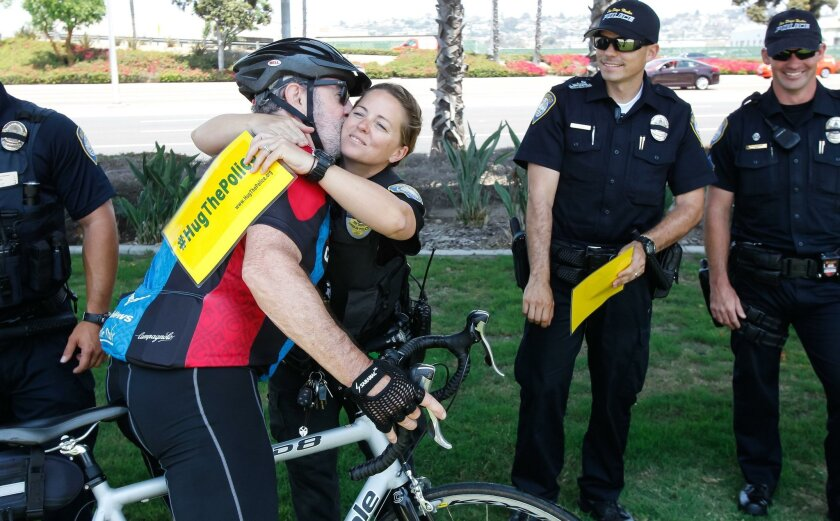 Ron Stein (left) kisses San Diego Harbor Police K-9 officer Traci Cain during a #HugThePolice event at Harbor Police Headquarters on Saturday in San Diego.