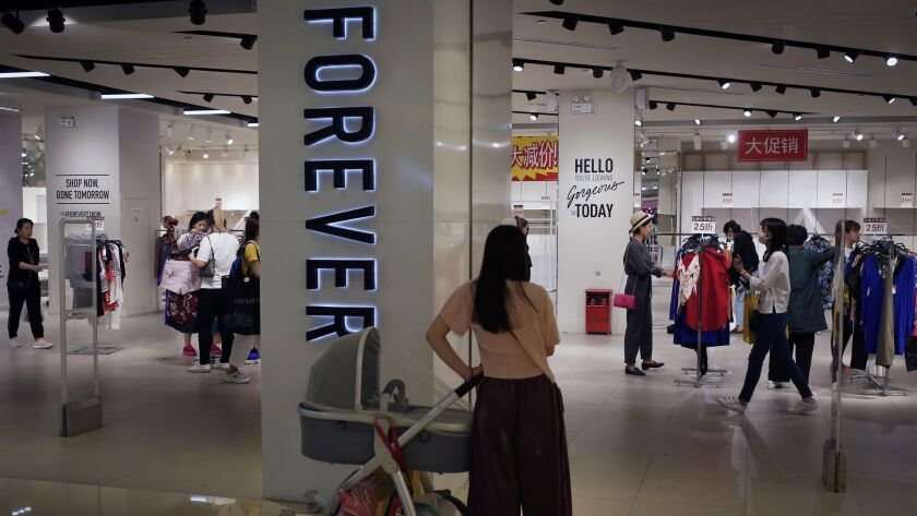 A woman watches as shoppers select clothing at a Forever 21 store in Beijing. The company is pulling out of the China market.