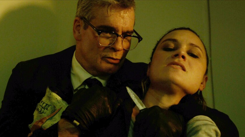 "Henry Rollins and Kristina Kiebe breaking all rules of social distancing in the thriller ""The Last Heist."""