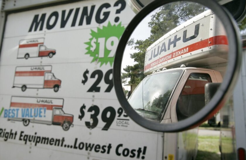 A U-Haul truck is seen in the side mirror of a another truck sitting on a dealer lot.