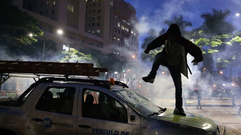 Protesters smash a car in Rio de Janeiro as thousands of Brazilians staged a general strike to protest pension and labor reforms being pushed by the conservative government of President Michel Temer.