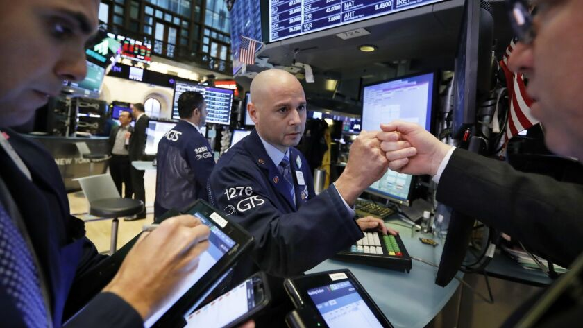 Specialist Mario Picone, center, works with traders Nov. 9 at his post on the floor of the New York Stock Exchange.