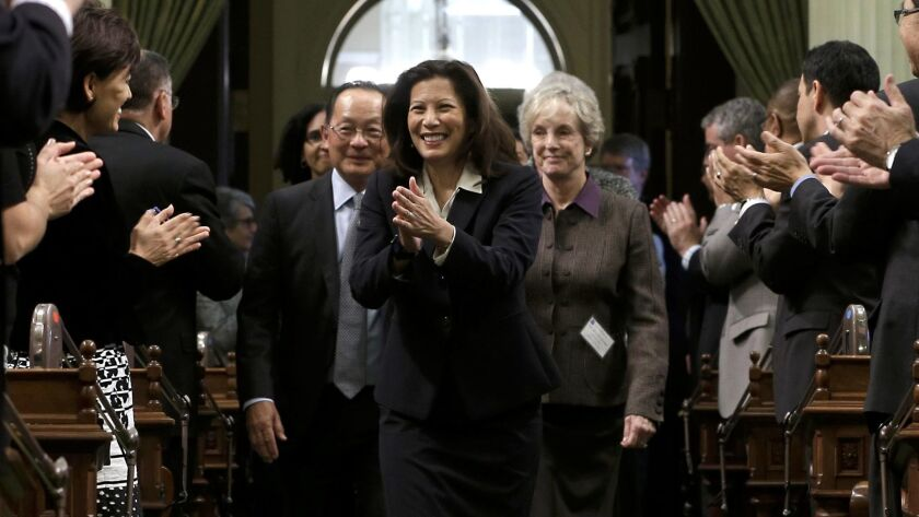 California Supreme Court Chief Justice Tani Cantil-Sakauye returns lawmakers' applause as she is esc