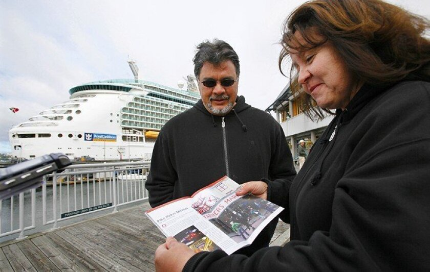 Philip and Yolanda Tabet of Belen, N.M., looked at a brochure of downtown Seattle as they walked past their cruise ship, the Royal Carribean Mariner of the Seas, shortly after it docked Thursday morning in Seattle.