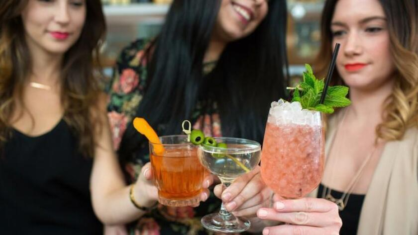 Mixologists Christy Spinella (from left), Adele Stratton and Meghan Balser toast at Ironside in Little Italy. (Brogen Jessup Photography)