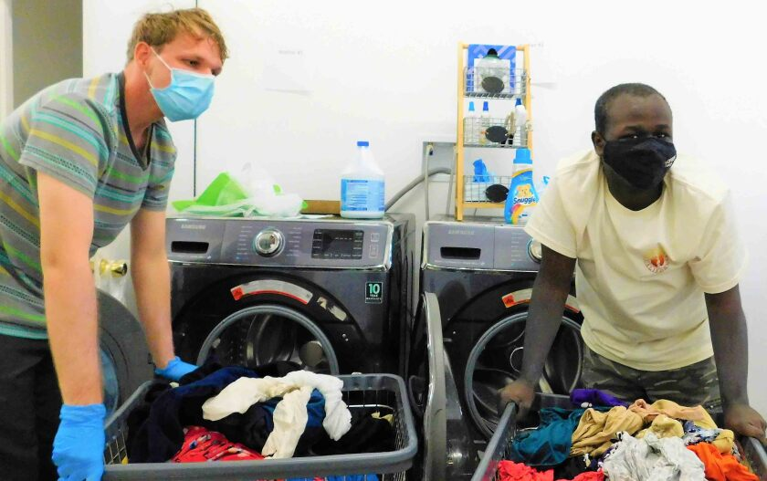Laundry Day workers Dakota Clark, left, and Lisco Scott transfer laundry from the washers to the dryers.