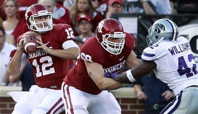 Oklahoma quarterback Landry Jones (12) passes as Lane Johnson blocks Kansas State defensive end Meshak Williams (42) during the first quarter of an NCAA college football game in Norman, Okla., Saturday, Sept. 22, 2012. (AP Photo/Sue Ogrocki)