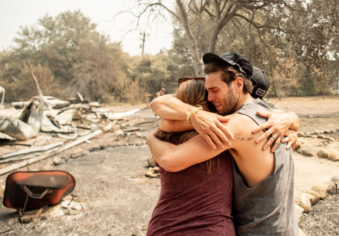 Family members embrace at the burned remains of their home in Vacaville, Calif.