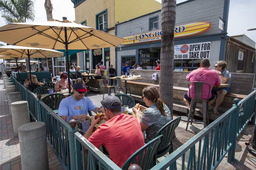 People eat out at The Longboard Restaurant and Pub in Huntington Beach on May 26.