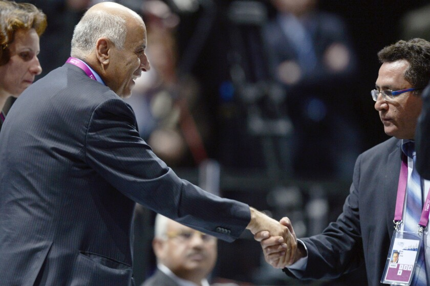 Palestinian Football Assn. President Jibril Rajoub, left, and Israeli Football Assn. chief Ofer Eini, shake hands after a contentious debate Friday over soccer events in disputed territory during the 65th FIFA Congress in Zurich, Switzerland.