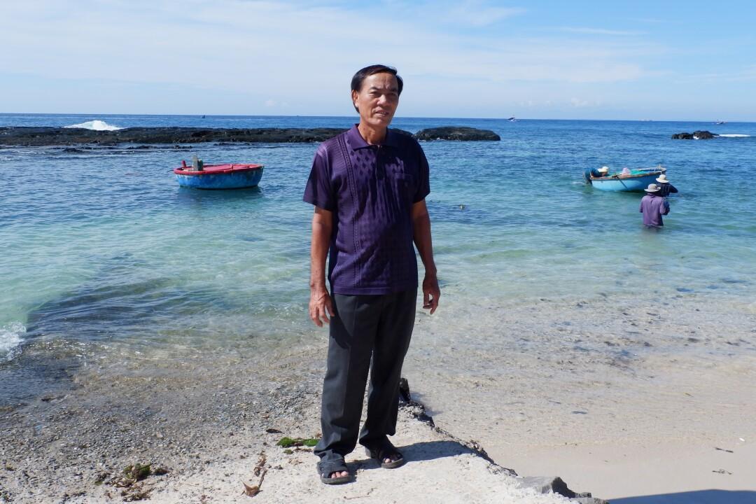Ein Mann steht am Strand vor ein paar kleinen Fischerbooten