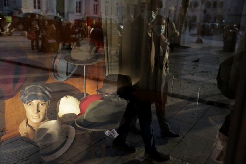 A couple wearing face masks are reflected on the window of a hat shop in downtown Lisbon, Wednesday, Dec. 2, 2020. (AP Photo/Armando Franca)