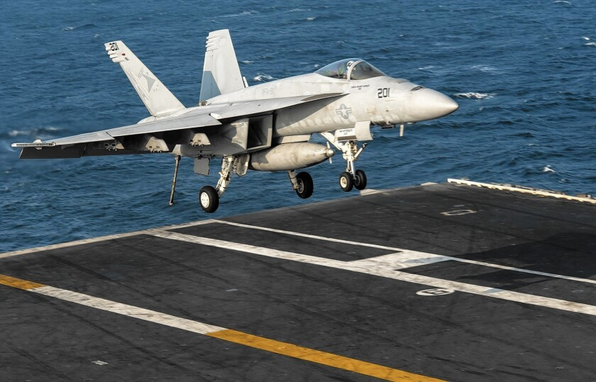 An F-18 lands on the flight deck of the aircraft carrier USS Carl Vinson in the Persian Gulf, part of operations targeting Islamic State militants in Iraq and Syria.