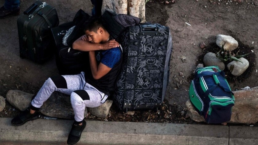 A man rests outside El Chaparral port of entry in Tijuana last month while he waits for his turn to present himself to U.S. border authorities to request asylum.