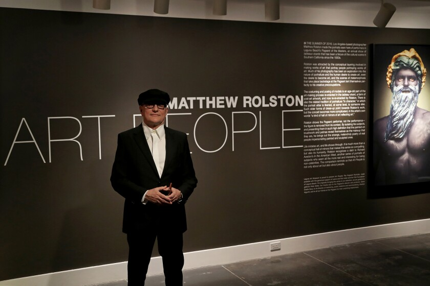 """Photographer Matthew Rolston poses in front of his exhibit, """"Art People: The Pageant Portraits."""""""